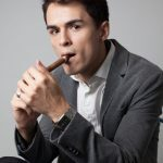 A man lighting a cigar practices common cigar etiquette.