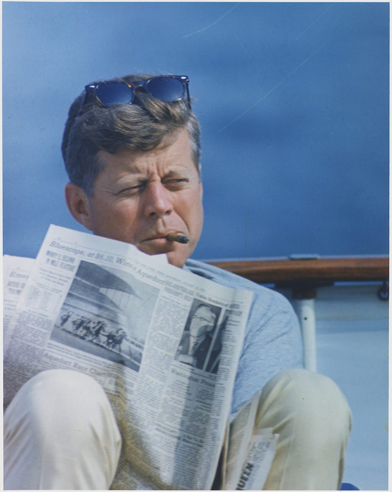 John F. Kennedy reading while smoking a cigar.