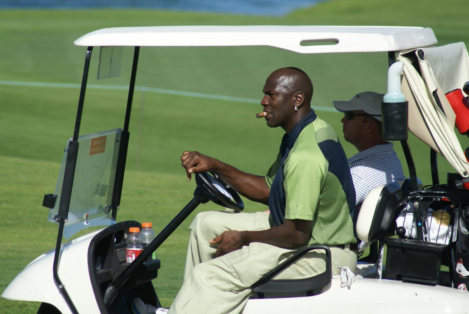 Michael Jordan smoking a cigar while driving a golf cart.