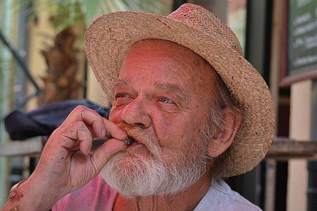 A man indulging in cigar smoking.