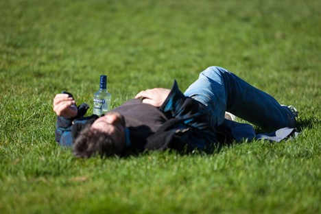 Man with a hangover lying in the grass with a bottle of water