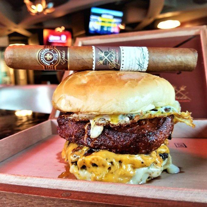 An after-dinner cigar resting on top of a burger