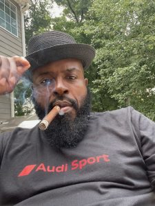 Boxing world champion, Yahya McClain enjoying a cigar outside